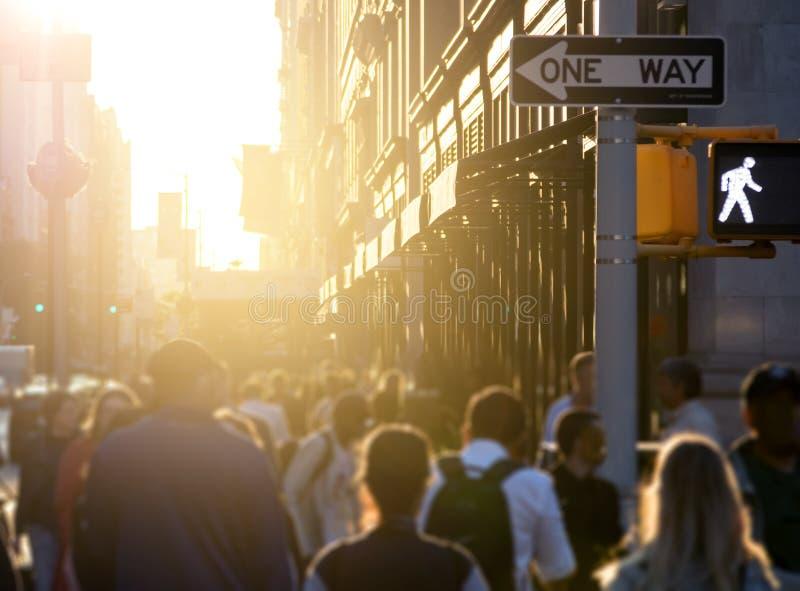 Tłum anonimowi ludzie chodzi w dół chodniczek z jaskrawym światłem słonecznym w tle na ruchliwej ulicie w środek miasta Manhattan fotografia stock