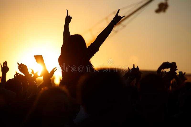 Tłum cieszy się lato festiwal muzyki, zmierzch sylwetek ręki up obrazy stock