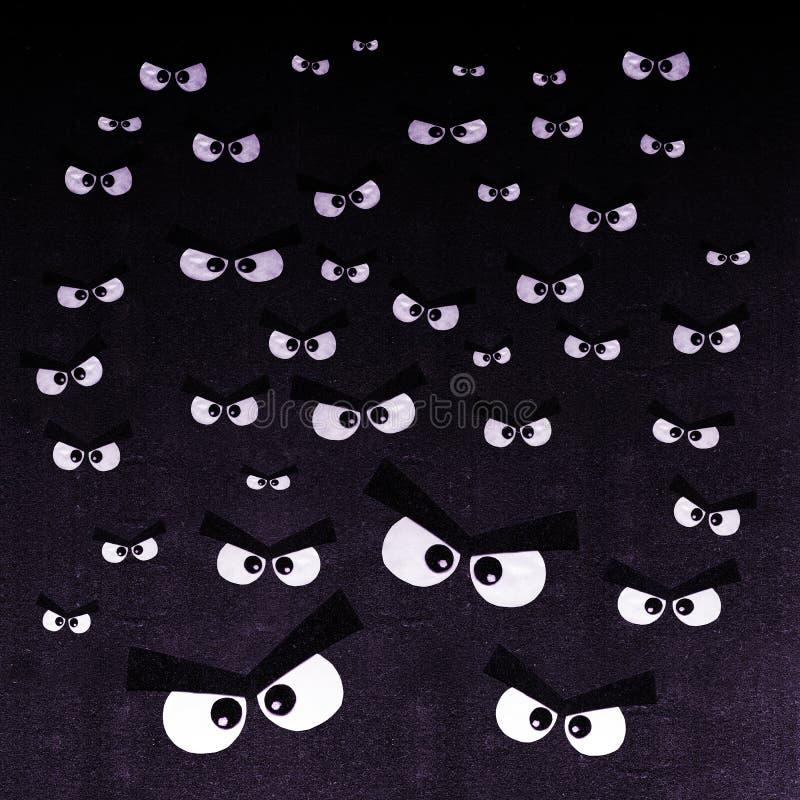 Tłum gniewni oczy na ciemnym tle