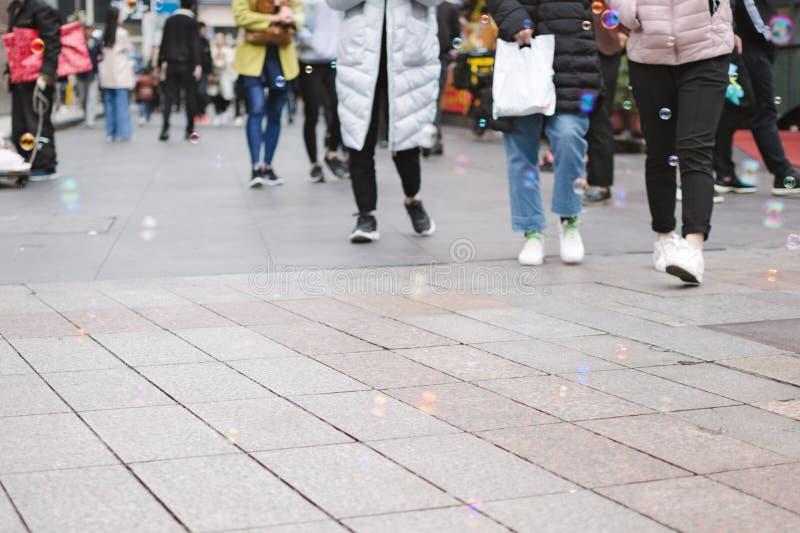 Tłum ludzie chodzi w miasto ulicie przez mydlanych bąbli obrazy stock