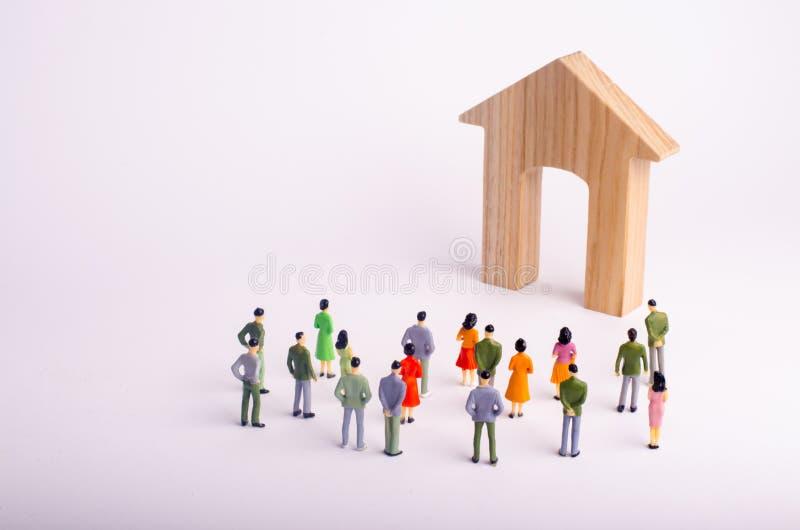 Tłum ludzie stoi drewnianego dom na białym tle i patrzeje Kupienie i sprzedawanie nieruchomość, czynsz Affordabl fotografia stock