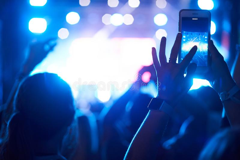 Tłum widownia z rękami używać kamera telefon brać obrazki i wideo przy żywym koncertem, smartphone nagrywa muzyka na żywo festiva zdjęcia royalty free