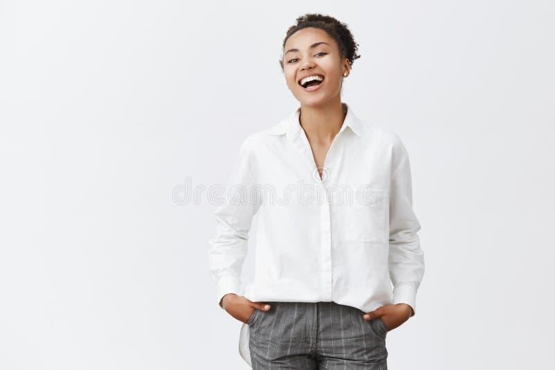 T恤杉和办公室裤子的悦目成功的深色皮肤的企业家,握在口袋和微笑的手 库存图片