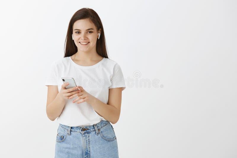 T恤杉和牛仔裤的,拿着智能手机和佩带无线的无忧无虑的时髦的女性办公室工作者水平的射击 库存图片