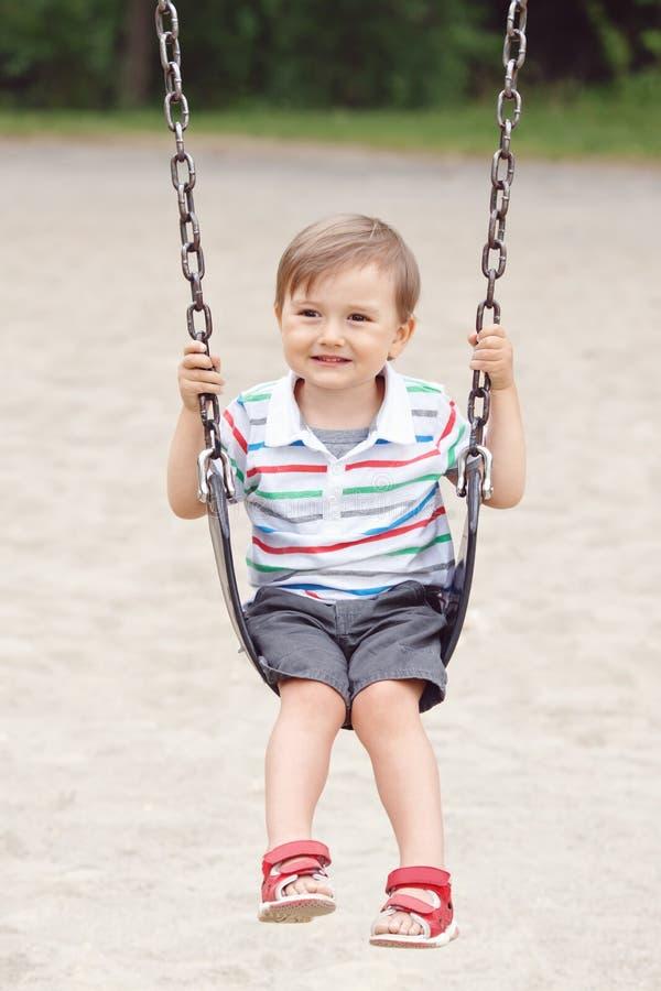 T恤杉和牛仔裤的愉快的微笑的小男孩小孩在后院操场的摇摆短缺外面 库存照片