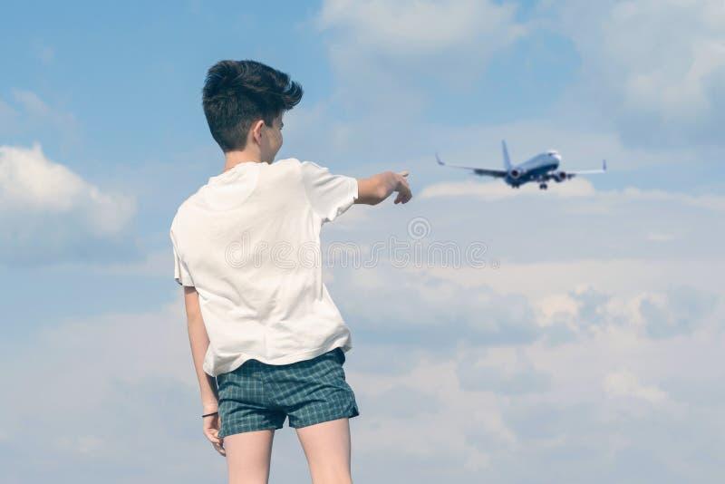 T恤杉和短裤的男孩显示他的在多云天空蔚蓝和使飞机降落的手指 免版税库存图片