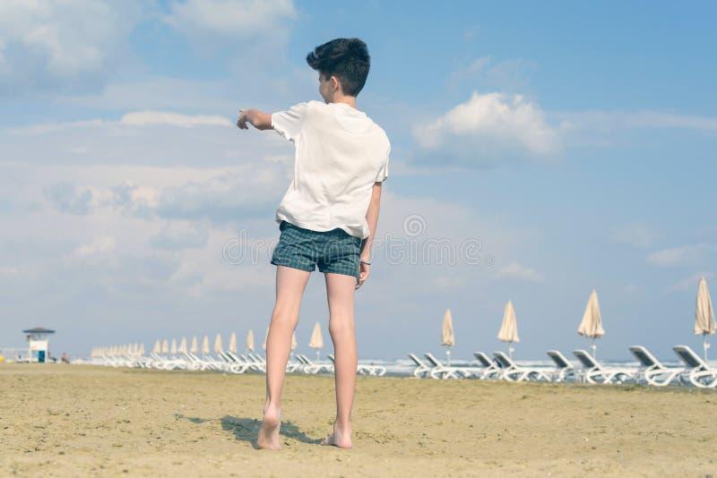T恤杉和短裤的男孩显示他的在多云天空蔚蓝和使飞机降落的手指 库存照片