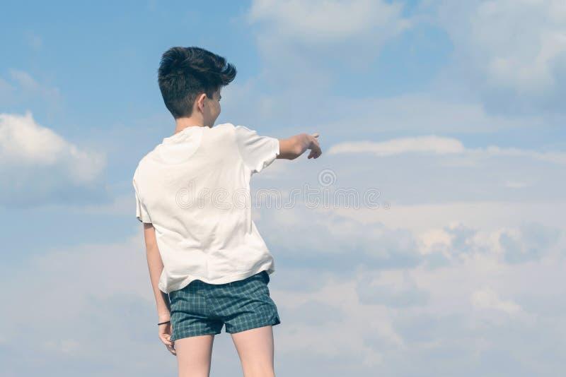 T恤杉和短裤的男孩显示他的在多云天空蔚蓝的手指 免版税图库摄影