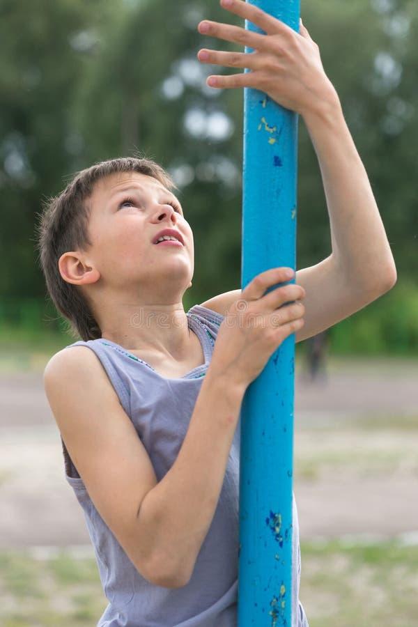 T恤杉的一个少年在一根体操杆上升 库存照片