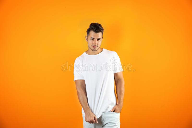 T恤杉的年轻人在颜色背景 库存图片