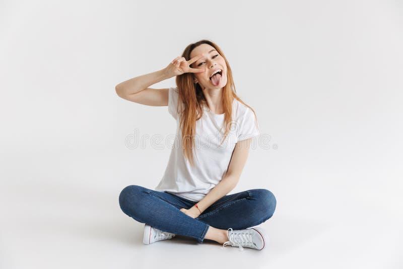 T恤杉的愉快的妇女坐地板 库存照片