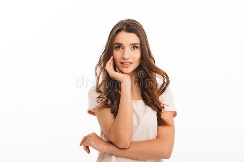 T恤杉的肉欲的微笑的深色的妇女在她的胳膊斜倚 免版税库存照片