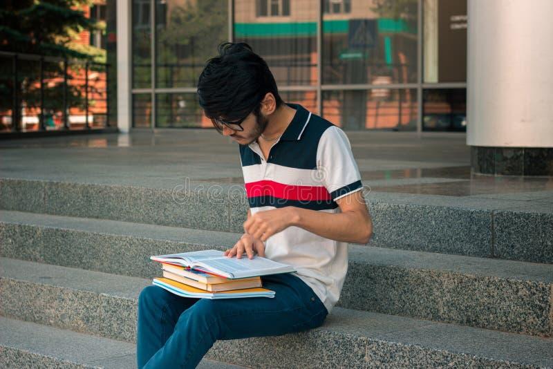 T恤杉的读在面孔的一名年轻学生和玻璃预定 库存图片