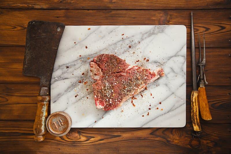 T-ben för nötköttbiff med tappningköttgaffeln på marmorbakgrunden royaltyfri bild