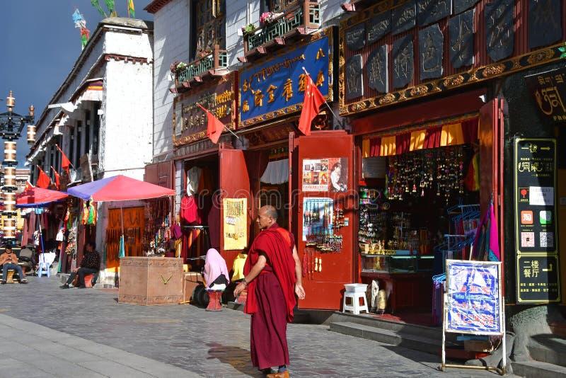 T?bet, Lasa, China, junio, 02, 2018 Monje que camina a lo largo de la calle antigua de Barkhor en un día de verano en tiempo nubl fotos de archivo libres de regalías