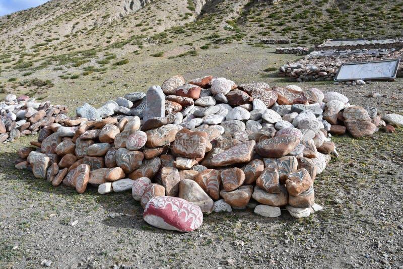 t?bet Piedras budistas del rezo con mantras y dibujos del ritual en el rastro de la ciudad de Dorchen alrededor del monte Kailash foto de archivo