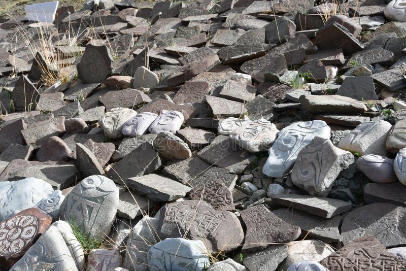 t?bet Piedras budistas del rezo con mantras y dibujos del ritual en el rastro de la ciudad de Dorchen alrededor del monte Kailash fotos de archivo