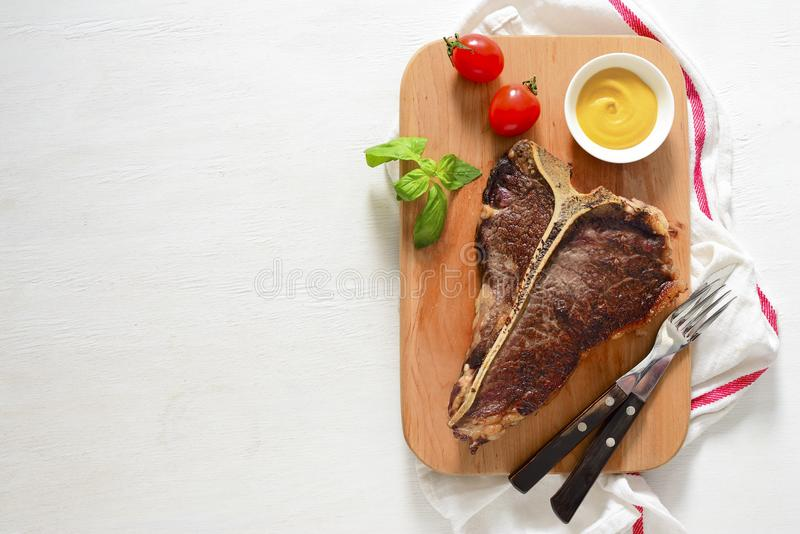 T-bone beef stake served on a cutting board royalty free stock photo