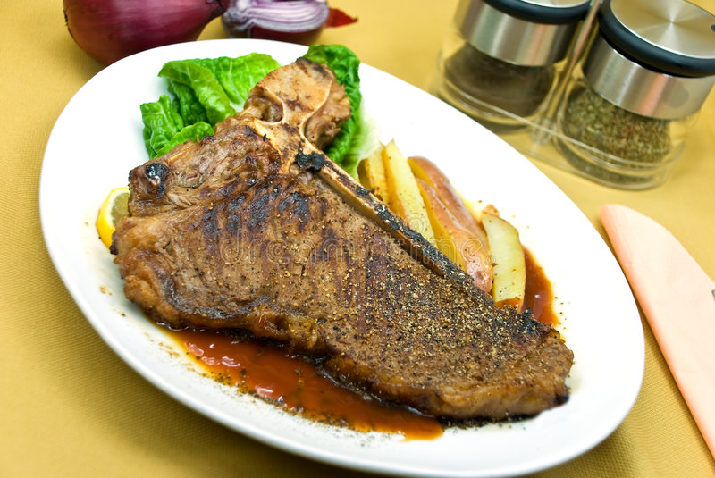 T - Bone Steak with fresh Salad and red Potatoes stock photography