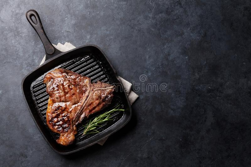 T-bone steak. Grilled T-bone steak on stone table. Top view with copy space stock image
