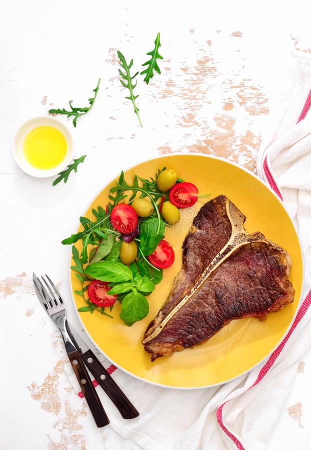 T-bone steak ready to eat, served on a plate, view from above stock image