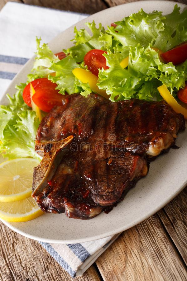 T-bone steak with salad of fresh vegetables and lemon close-up. T-bone steak with salad of fresh vegetables and lemon close-up on a plate. vertical stock photos
