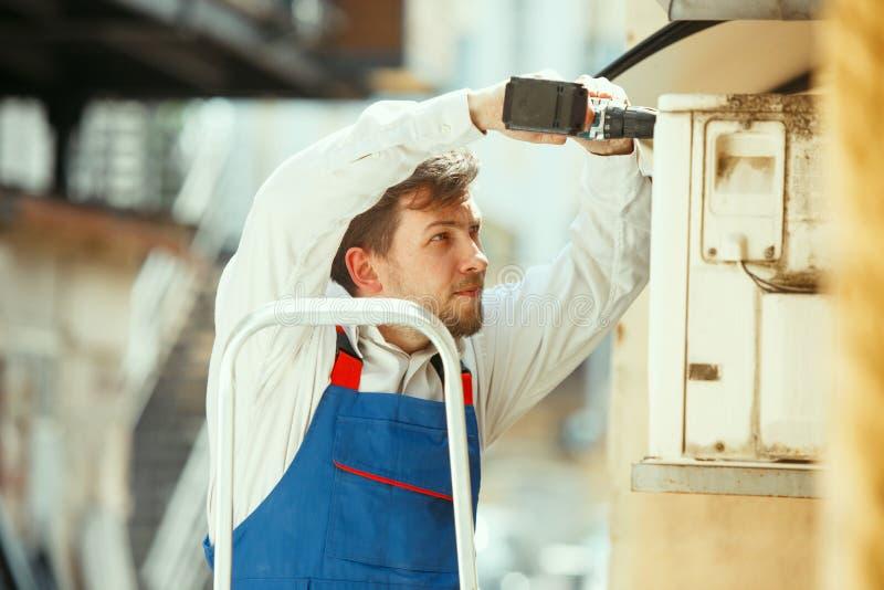 T?cnico da ATAC que trabalha em uma pe?a do capacitor para a unidade de condensa??o imagem de stock royalty free