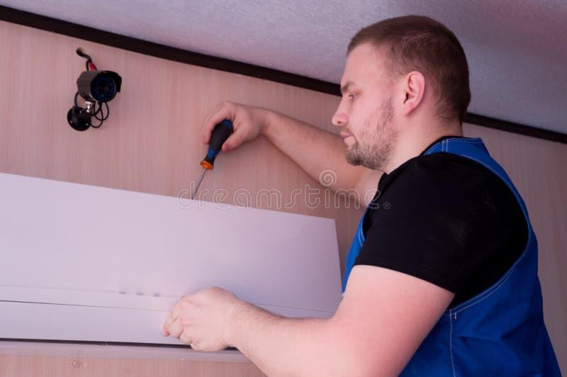 T?cnico de sexo masculino que repara el acondicionador de aire dentro foto de archivo libre de regalías
