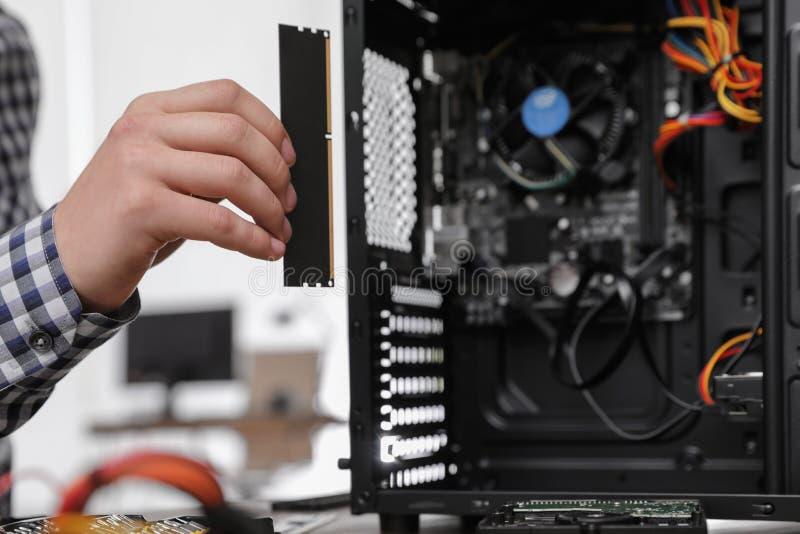 T?cnico masculino que p?e a microplaqueta de RAM na unidade de sistema Reparo do computador imagens de stock