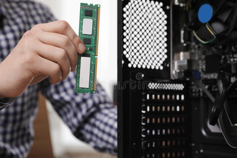 T?cnico masculino que p?e a microplaqueta de RAM na unidade de sistema Reparo do computador imagem de stock