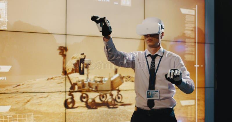 T?cnico que usa luvas dos auriculares e do exoskeleton de VR imagens de stock