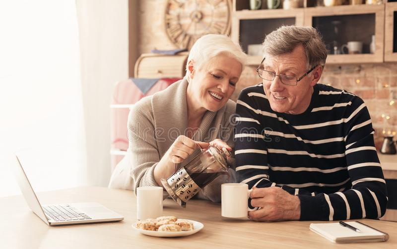 T? de consumici?n de los pares mayores felices en cocina imagenes de archivo