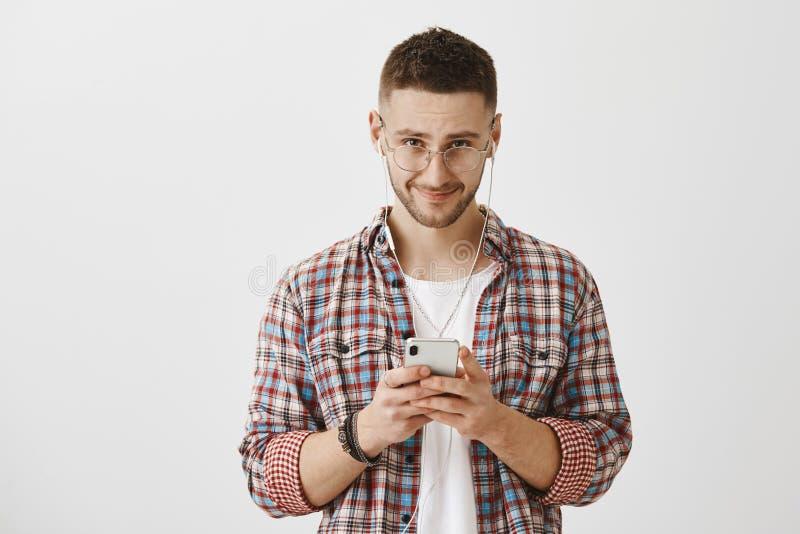 ` T de Don que vous voyez que je suis dans des écouteurs Jeune mâle beau tracassé avec la barbe regardant de dessous le front l'a photographie stock libre de droits