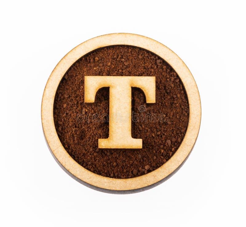 T, drewniany abecadło list - Zmielona organicznie kawa Odgórny widok zdjęcie royalty free