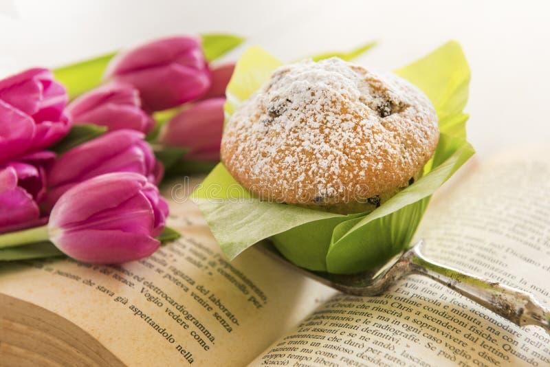 T? e muffin con le tazze bollenti verdi con i tulipani immagine stock