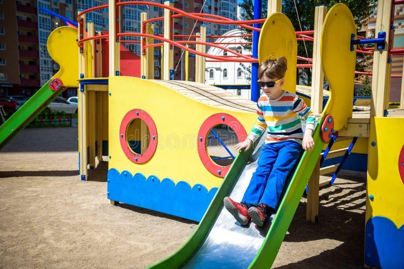 ?t?, enfance, loisirs, amiti? et concept de personnes - le petit gar?on heureux sur le terrain de jeu d'enfants a gliss? de la co image libre de droits