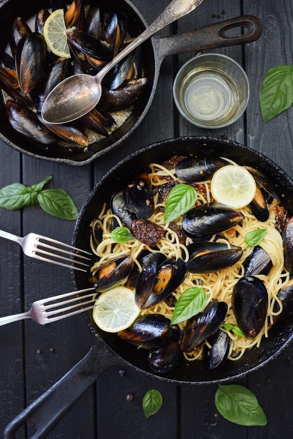 t?t frig?rande pannapastaskaldjur upp Läcker spagetti med musslor, basilika, citronen och vitt vin i gjutjärnpannor på svart bakg royaltyfria foton