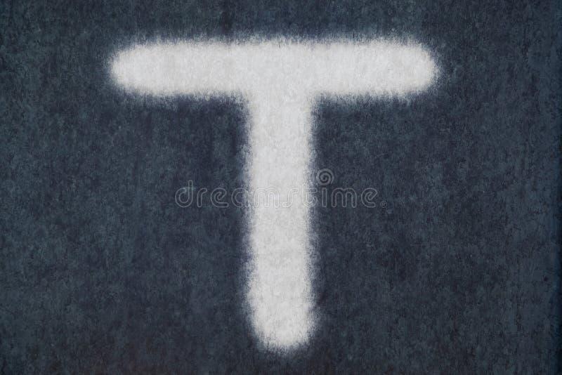 T isolerad kritabokstav i svart tavlabakgrund arkivbild