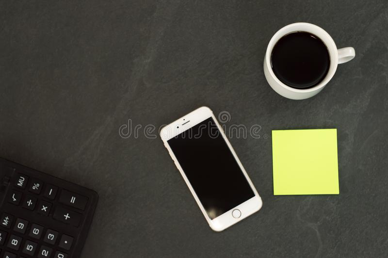 T?l?phone blanc avec une tasse de caf?, d'un stylo rouge et d'un mensonge de calculatrice sur une table en bois blanche photo stock