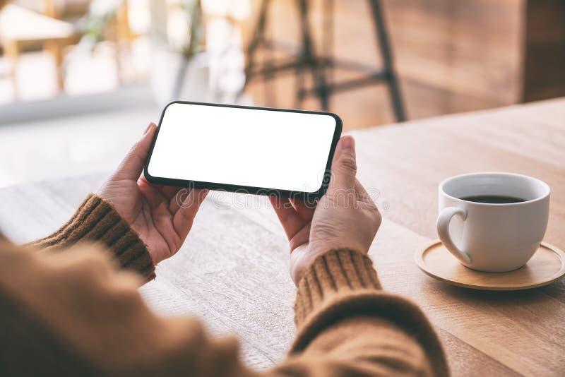 T?l?phone portable de noir de participation de la main de la femme avec l'?cran vide horizontalement avec la tasse de caf? sur la photo libre de droits