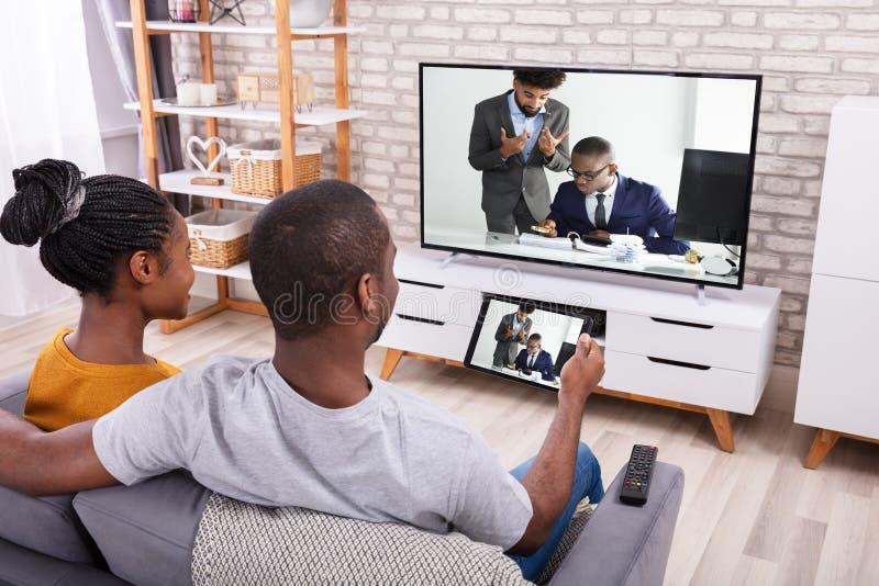 T?l?vision se reliante de couples par la radio sur la Tablette photographie stock