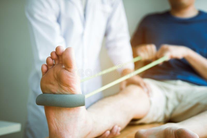 T?lmodig bruksmotst?ndsmusikband som ut str?cker hans ben med hj?lp f?r fysisk terapeut i klinikrum royaltyfri fotografi