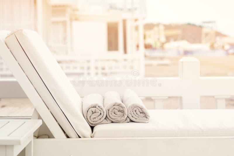 T?m sunbed med sl?gna in handdukar p? en h?rlig strand arkivbilder