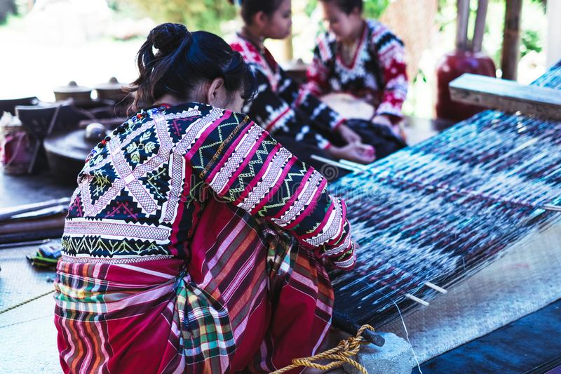 T`nalak cloth weaving. Koronadal, PH - July 16, 2016: Rare view of the T`boli woman in traditional clothing hand woven the sacred T`nalak cloth using Abaca plant royalty free stock images