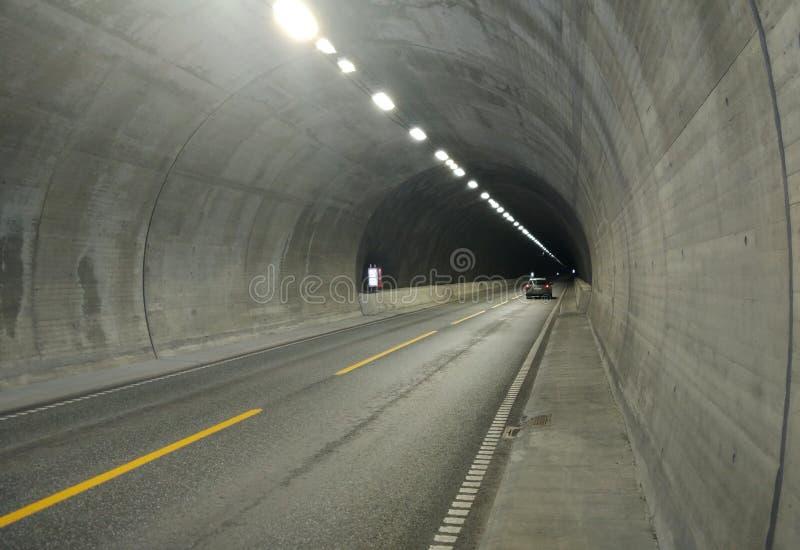 T?nel del camino de la carretera Los coches se mueven en un t?nel a trav?s de una monta?a en una autopista sin peaje fotografía de archivo