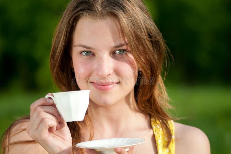 T quente da bebida bonita da mulher nova ao ar livre imagens de stock