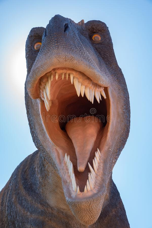 Scary T-Rex Dinosaur Roars up close. T-Rex dinosaur roaring and showing all his teeth being very intimidating stock photo