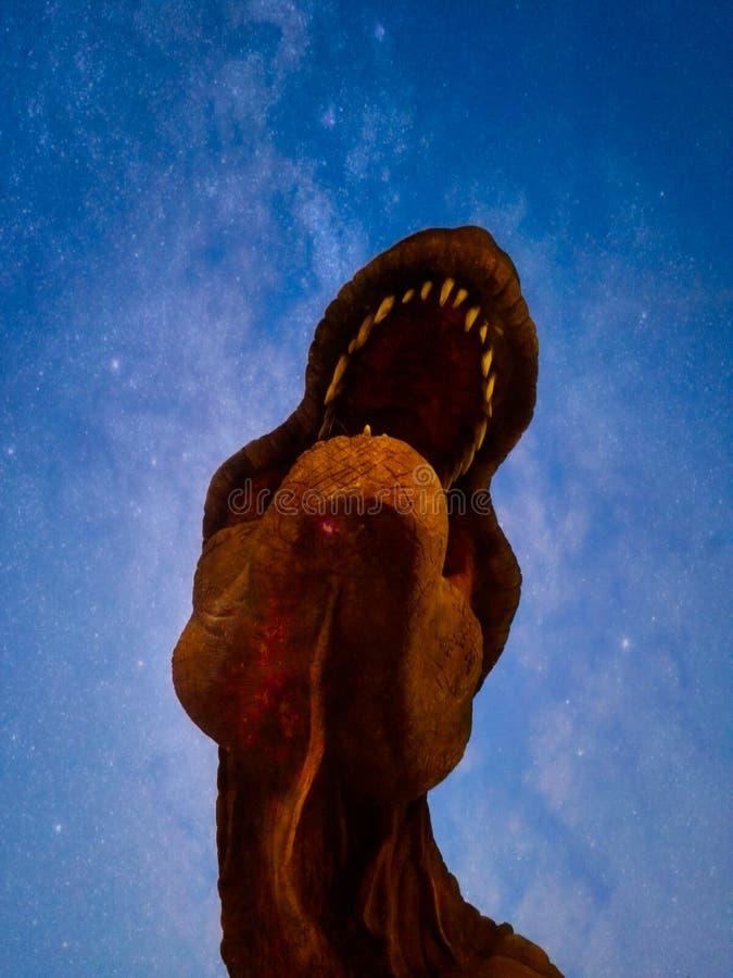 T-Rex styrka som ser den stjärnklara himlen arkivbild