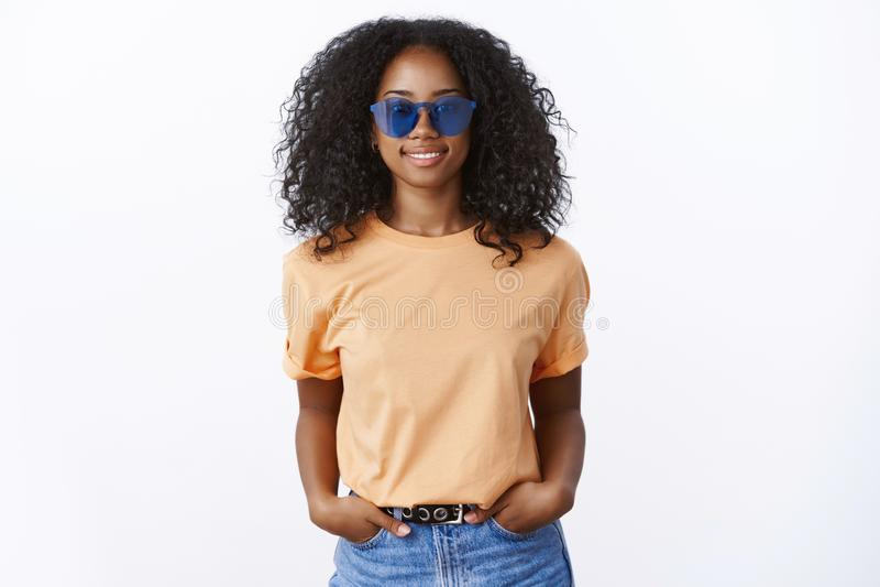T-shirt alaranjado vestindo dos óculos de sol da menina afro-americano à moda fresca atrativa que mantém bolsos das mãos seguros, imagem de stock royalty free
