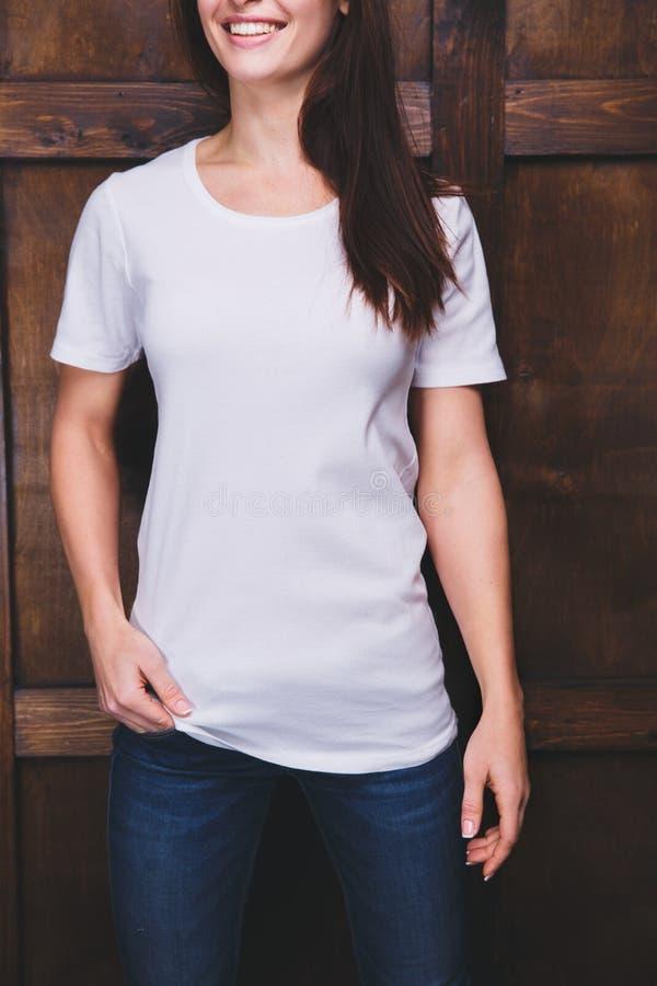 T-shirt blanc de port de femme devant le mur en bois photo stock